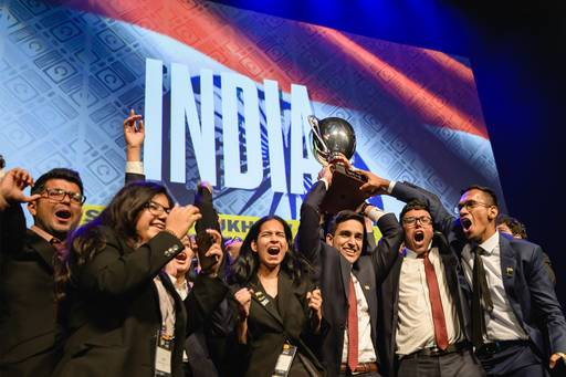 Students wearing business suits and holding trophy in front of India banner