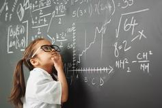 Young girl thinking in front of blackboard
