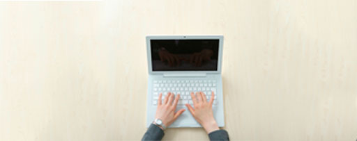Hands on keyboard of white laptop
