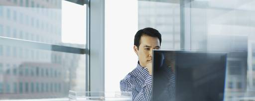 Businessman wearing check pattern shirt sitting in front of desktop