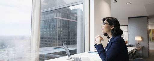 Pensive businesswoman at laptop looking out urban office window