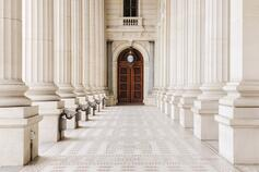 Marble columns and wooden door entrance to beautiful building