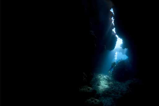 a female scuba diver in an underwater cave with sunbeams