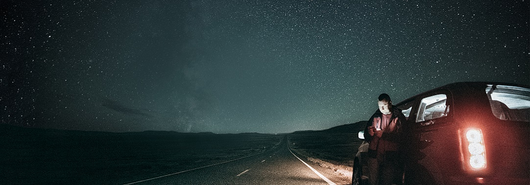 Man standing against his car at night under a starry night