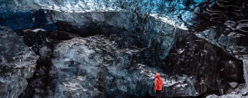 Man in red jacket looking up in a cave
