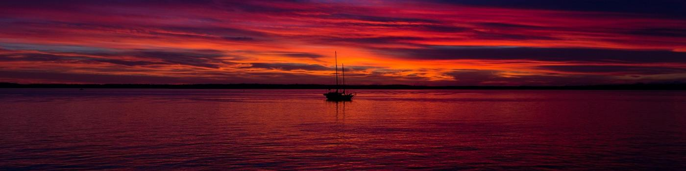 Sailboat at red sunset over water