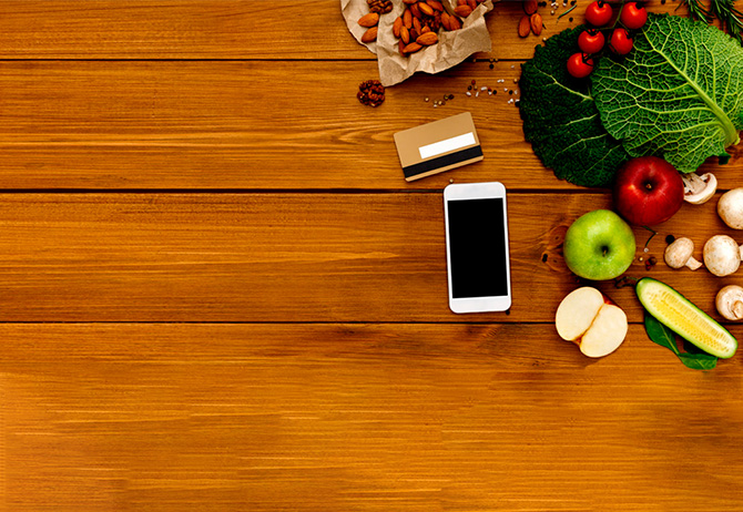 Fruits, vegetables, phone and card on wooden table