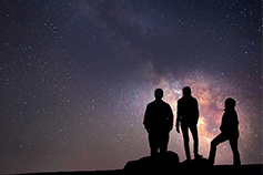 Three people standing under start in night sky