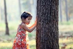 Young girl next to tree in forest