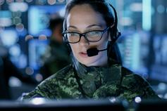 Female military officer wearing a headset and glasses while looking at a screen