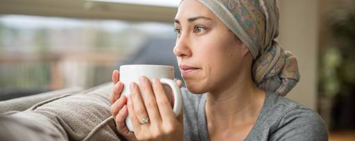 Ethnic young woman with cancer drinking cup of tea