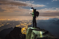 Hiker checks his device on the top of mountain