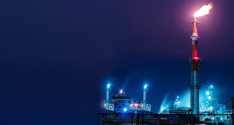 Low Angle View Of Oil Refinery Tower light on top in Night