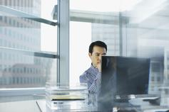 Man sitting in office and looking into computer screen