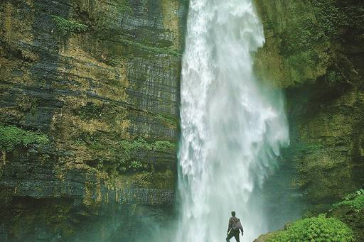 Man standing in front of waterfall and greenery around