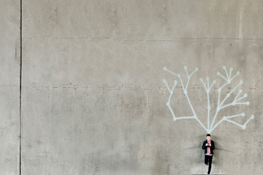 Man using phone standing against grey wall with graffiti