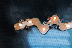 Panoramic overhead view of several business meetings going over curvy table