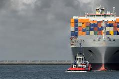 Ship loaded with heavy containers in sea against cloudy sky