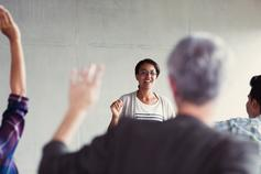 Woman with spectacles conducting a session and people raising hands