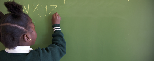 Close up shot of schoolgirl writing the alphabet on a chalkboard