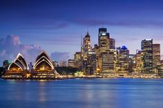 The Sydney Opera House and Circular Quay district, seen under a purplish sky at dusk.