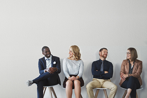 Four business people sitting on chairs against a wall