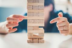 Hand removing block from middle of Jenga game