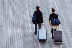 Two people walking along with suitcases on wheels