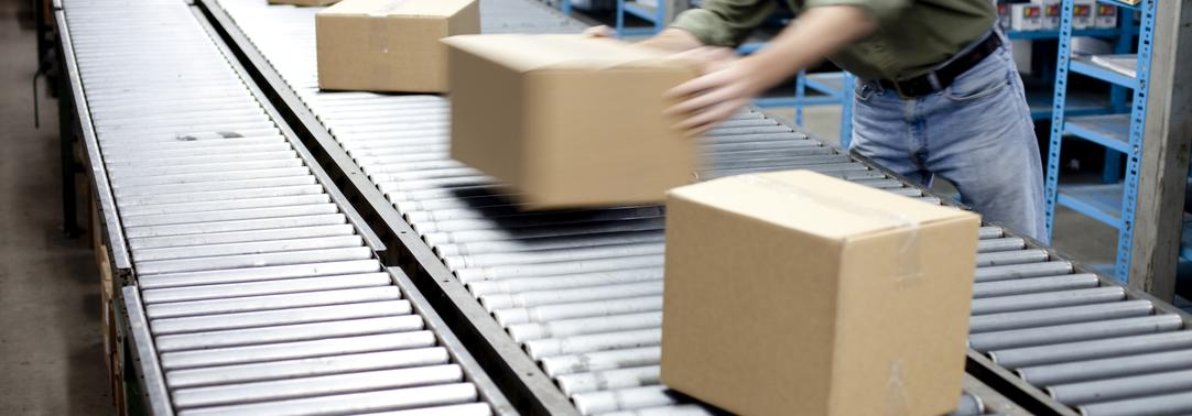 Man working with boxes on long conveyor belt