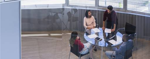 Four people holding a meeting in a glass office