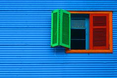 Red and green color open window against blue wall