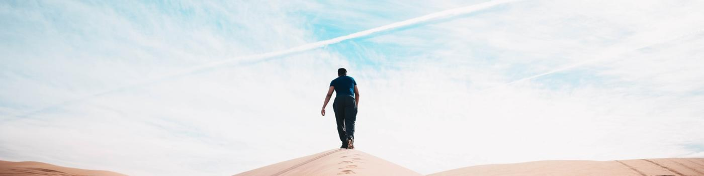 Man walking up a desert hill