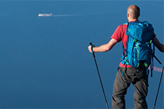 Back view mountain climber wearing red shirt and blue bag