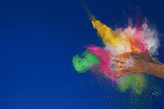 Colorful powder burst cloud formed by clapping hands against blue background