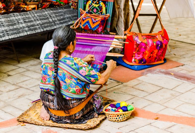 Back view of an old lady working on cloth to make bags, Americas Guide Guatemala