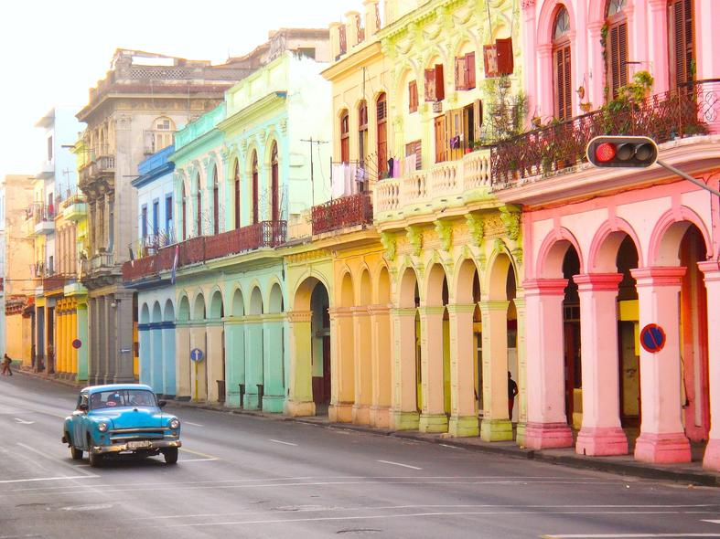 Blue car infront of colourful buildings