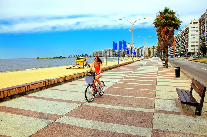 Girl riding bicycle by the beach Uruguay