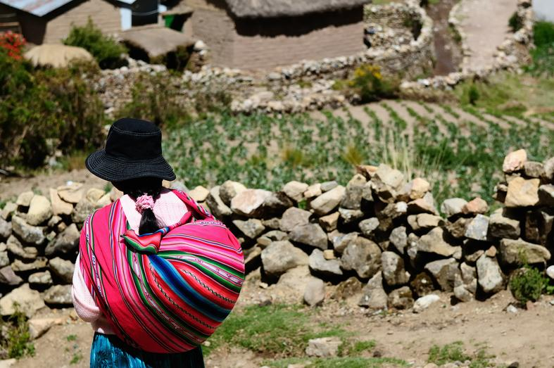 Lady carrying pink cloth bundle on her back Bolivia
