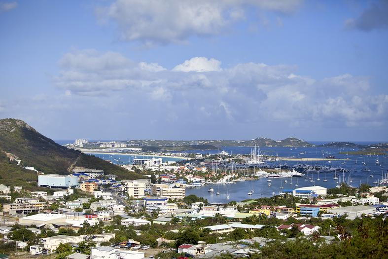 Small mountain and port view with houses, boats and trees against-blue-sky, Americas Guide Sint Maarten