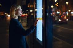 Woman standing in front of large outdoor touchscreen