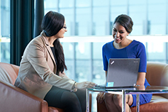 Two women wearing formals and discussing business on laptop in a meeting