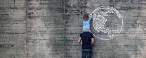 Girl sitting on man's shoulder drawing on wall