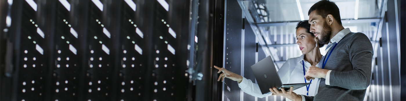 Man woman standing with laptop in data center
