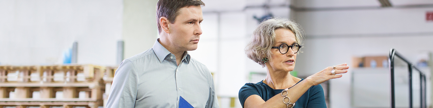 Woman with tab guiding man with folder in a store