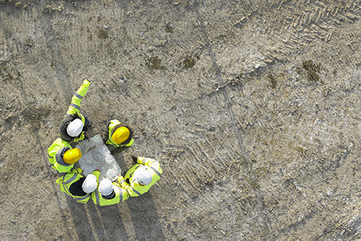Aerial view of six construction workers wearing yellow & white caps, holding map