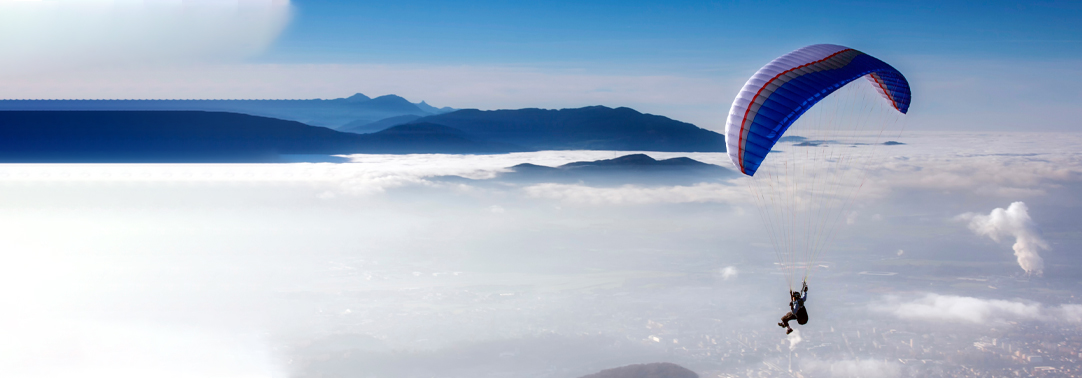 Man flying on parachute above clouds