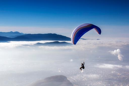 Man flying on parachute above the clouds