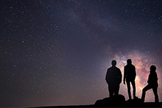Silhouettes of three people staring at the night sky