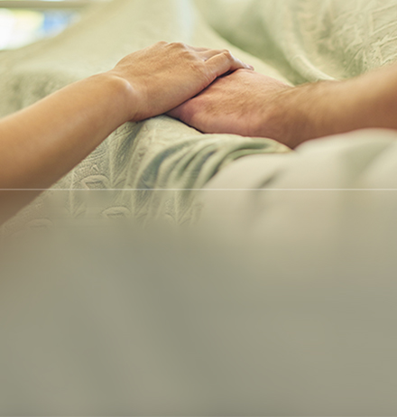 Visitor holds a patient's hand in hospital bed