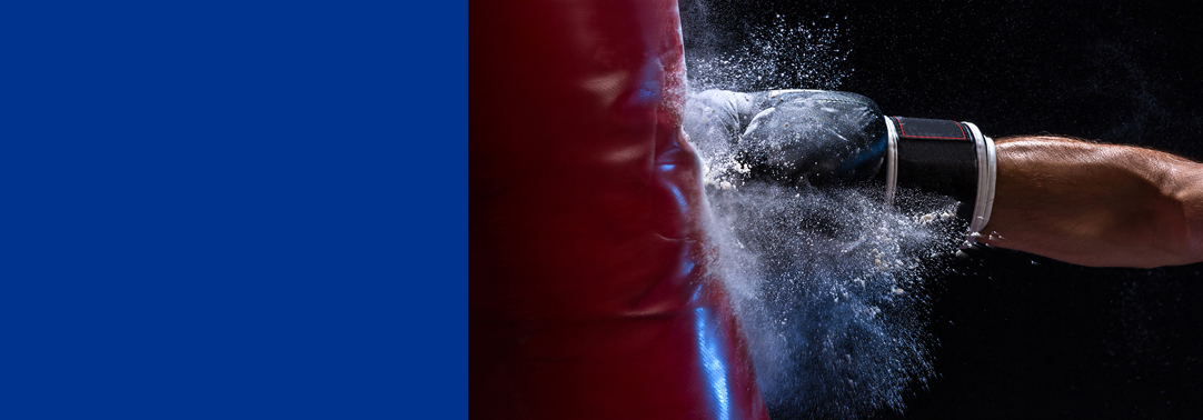 Hand in boxing glove hitting red punching bag